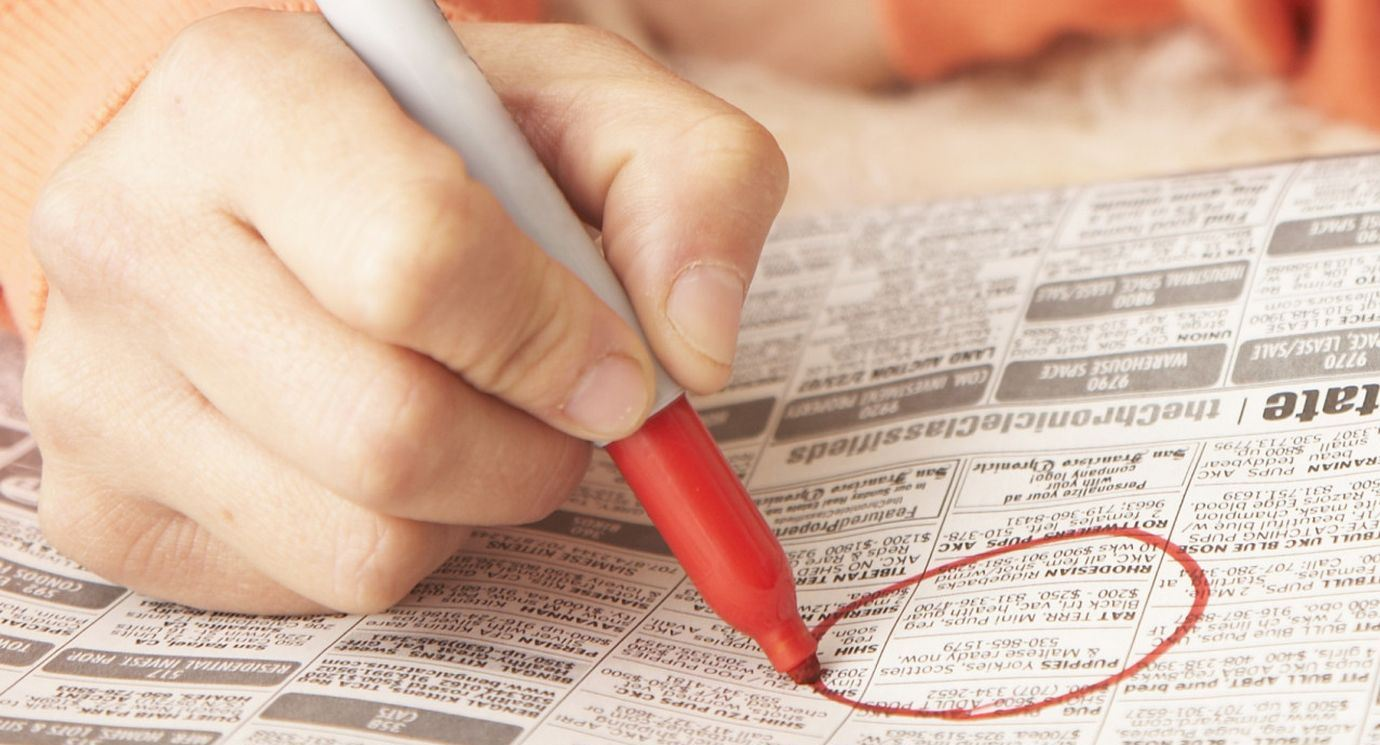 Woman circling classified ad in newspaper, close-up